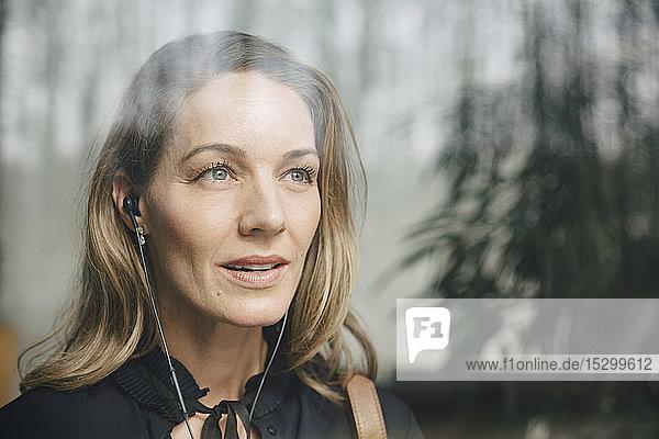 Blonde Geschäftsfrau hört Musik über Kopfhörer  während sie im Büro wegschaut Blonde Geschäftsfrau hört Musik über Kopfhörer, während sie im Büro wegschaut