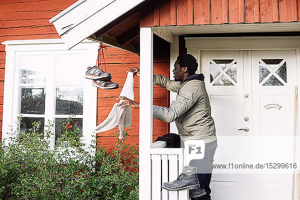 Side view of young man drying clothes while standing outside cottage
