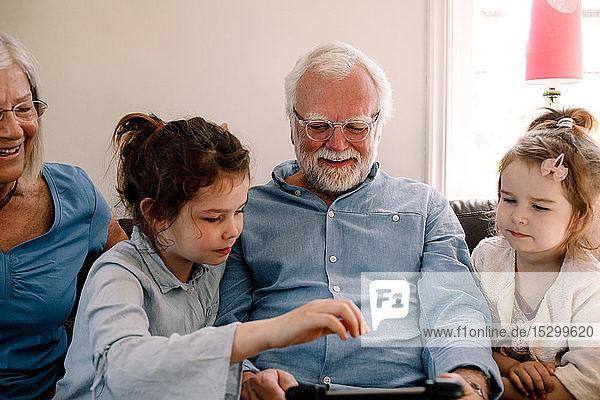 Smiling grandparents sitting with grandchildren while looking at digital tablet in living room at home