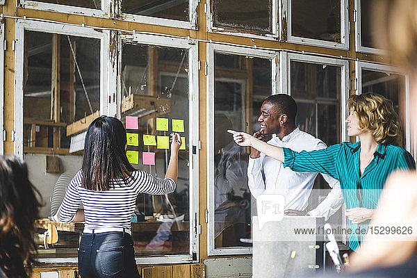 Selbstbewusste Computerprogrammierer  die ihre innovativen Ideen bei Besprechungen am Arbeitsplatz mit Haftnotizen festhalten Selbstbewusste Computerprogrammierer, die ihre innovativen Ideen bei Besprechungen am Arbeitsplatz mit Haftnotizen festhalten