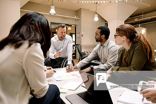 Serious colleagues looking at disabled manager while working in office