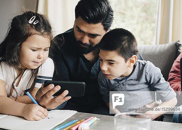 Vater zeigt Kindern ein Smartphone  während eine Frau einen Laptop auf dem Sofa im Wohnzimmer benutzt