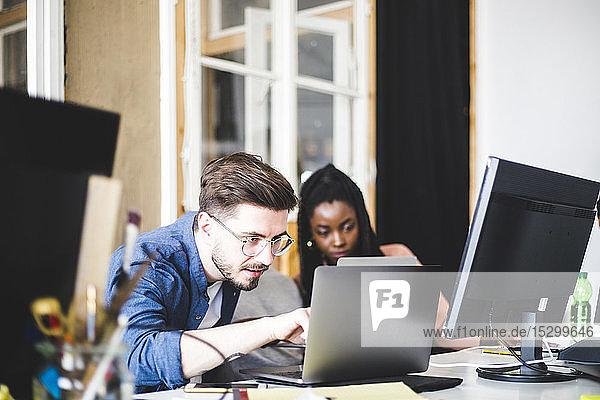Junger Computerexperte kodiert in Laptop  während er mit einer Kollegin am Arbeitsplatz arbeitet