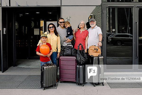 Porträt einer glücklichen Familie mit Gepäck steht am Hoteleingang