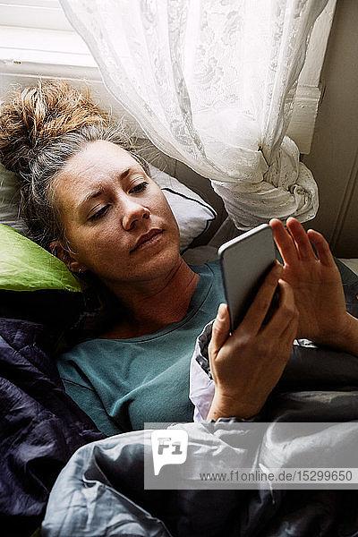 Hochwinkelansicht einer mittelgroßen erwachsenen Frau  die ein Smartphone benutzt  während sie auf einem Bett in einer Hütte liegt
