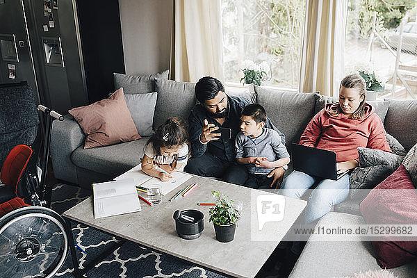 Hochwinkelansicht einer Familie  die zu Hause im Wohnzimmer sitzt