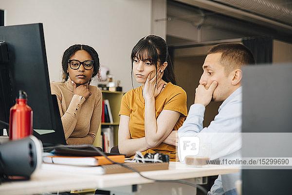 Fokussierte Computerprogrammierer schauen auf den Laptop  während sie gemeinsam am Schreibtisch im Kreativbüro arbeiten Fokussierte Computerprogrammierer schauen auf den Laptop, während sie gemeinsam am Schreibtisch im Kreativbüro arbeiten
