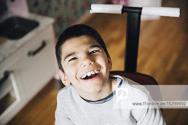 Hochwinkelansicht eines glücklichen behinderten Jungen  der zu Hause im Rollstuhl sitzt Hochwinkelansicht eines glücklichen behinderten Jungen, der zu Hause im Rollstuhl sitzt