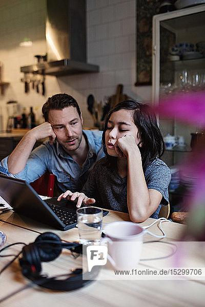 Vater betrachtet Sohn beim E-Learning mit Laptop auf dem Tisch zu Hause