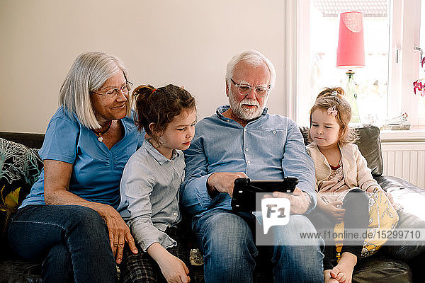 Grandparents sitting with grandchildren while using digital tablet in living room at home