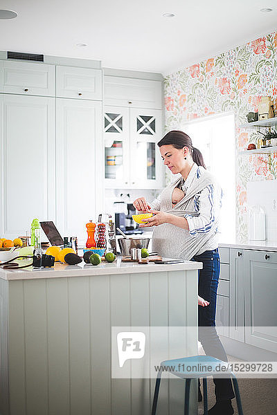 Working mother blogging in kitchen while carrying daughter in baby carrier at home