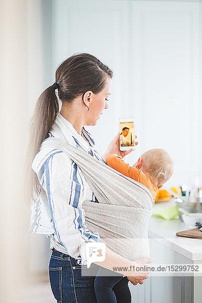 Seitenansicht einer weiblichen Bloggerin  die Fotobotschaften verschickt  während sie ihre Tochter zu Hause in der Küche trägt Seitenansicht einer weiblichen Bloggerin, die Fotobotschaften verschickt, während sie ihre Tochter zu Hause in der Küche trägt