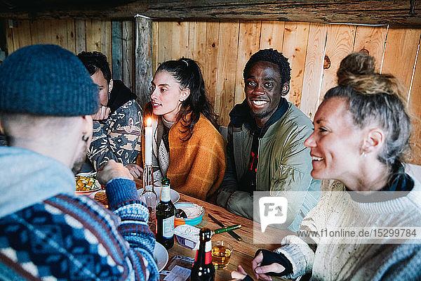 Porträt eines jungen Mannes  der sich mit Freunden unterhält  während er im Blockhaus beim Essen sitzt
