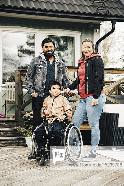 Portrait of smiling parents standing by disabled son sitting on wheelchair against house