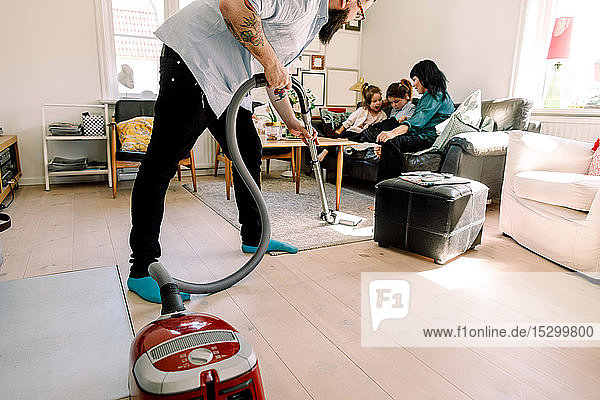 Man cleaning floor with vacuum cleaner while family sitting on sofa