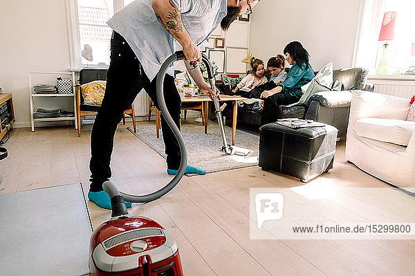 Mann reinigt den Boden mit dem Staubsauger  während die Familie auf dem Sofa sitzt