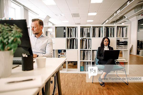 Seriöser Geschäftsmann arbeitet am Büroschreibtisch,  während eine Kollegin im Hintergrund einen Laptop benutzt