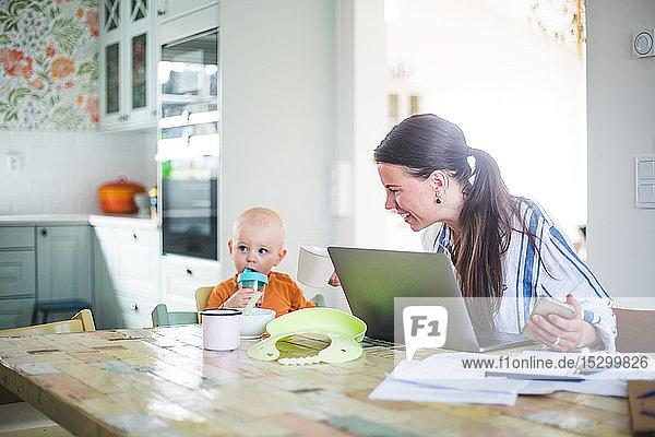 Lächelnde berufstätige Mutter im Gespräch mit Tochter  während sie freiberuflich am Esstisch in der Küche arbeitet