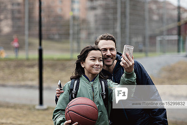 Smiling son taking selfie with father after basketball practice in winter