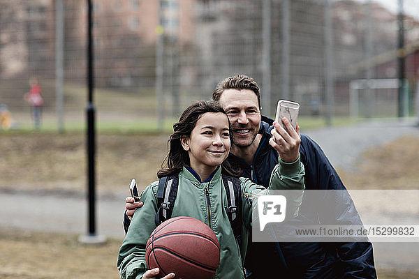 Lächelnder Sohn nimmt sich nach Basketballtraining im Winter mit dem Vater ein Lächelnder Sohn nimmt sich nach Basketballtraining im Winter mit dem Vater ein