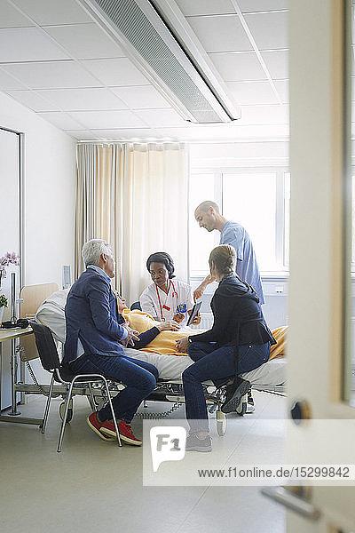 Mitarbeiter des Gesundheitswesens diskutieren mit der Patientin und ihren Freunden auf der Krankenhausstation