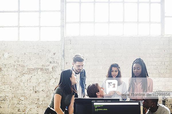 Professionelle Programmierer  die im Team arbeiten  während sie am kreativen Arbeitsplatz programmieren