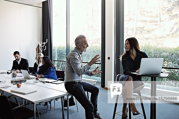 Senior businessman discussing to businesswoman using laptop with colleagues working at conference table in board room