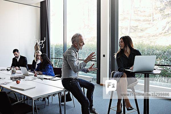 Leitender Geschäftsmann diskutiert mit Geschäftsfrau am Laptop mit Kollegen  die am Konferenztisch im Sitzungssaal arbeiten