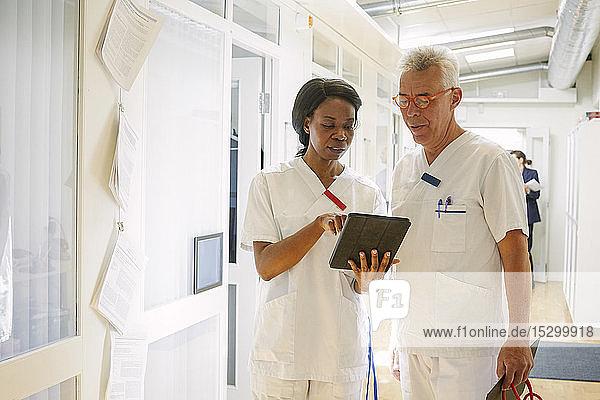 Männliche und weibliche Ärzte diskutieren über digitales Tablet im Krankenhauskorridor