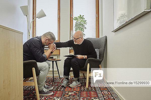 Therapeut tröstet reifen Patienten während der Therapiesitzung Therapeut tröstet reifen Patienten während der Therapiesitzung