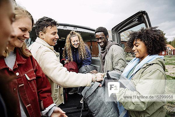 Lächelnde Frau reicht im Auto stehend Rucksäcke an Freunde weiter Lächelnde Frau reicht im Auto stehend Rucksäcke an Freunde weiter