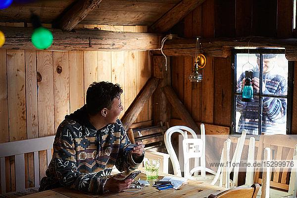 Mann fotografiert Freund beim Online-Shopping im Ferienhaus vom Fenster Mann fotografiert Freund beim Online-Shopping im Ferienhaus vom Fenster