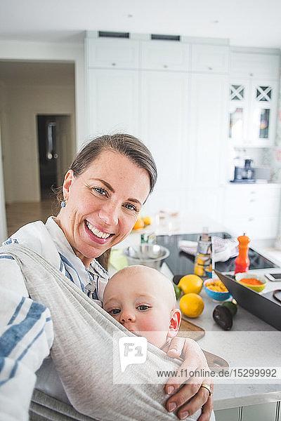 Porträt einer lächelnden Food-Bloggerin  die ihre Tochter zu Hause in der Küche trägt