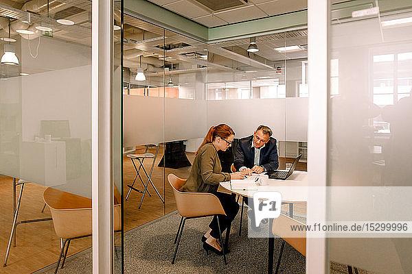 Vertriebsleiter diskutieren über Geschäftspläne  während sie am Arbeitsplatz mit Blick durch die Tür sitzen
