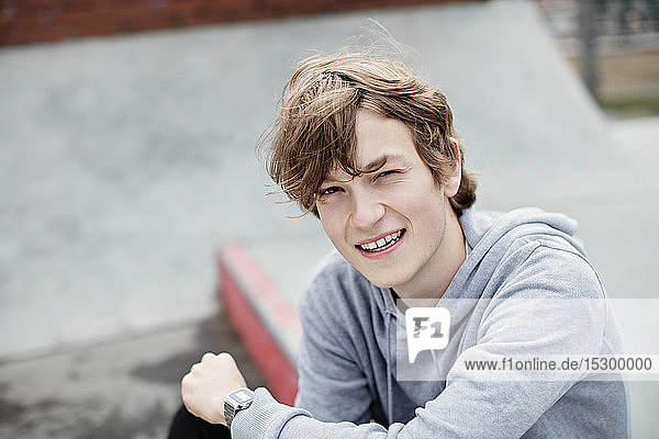 Porträt eines lächelnden Teenagers mit Kapuzenhemd  der in der Stadt auf dem Bürgersteig sitzt