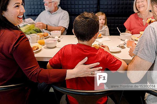 Lächelnde Frau schaut weg  während die Familie beim Frühstück im Restaurant sitzt