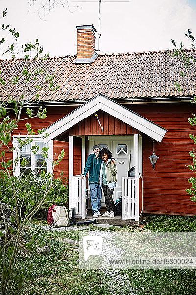 Porträt von lächelnden Freunden mit Rucksäcken  die am Wochenende vor der Hütte stehen