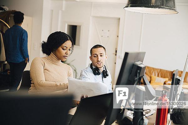 Weibliche Computerhackerin zeigt einem männlichen Kollegen ein Dokument  während sie im Büro sitzt