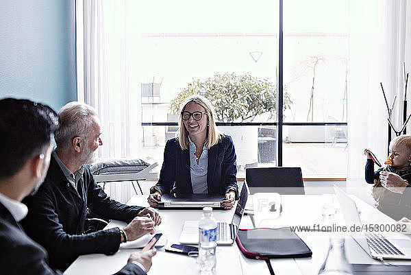Smiling businesswoman discussing with colleagues at conference table in board room