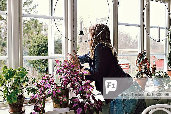 Frau schließt Fenster im Zimmer zu Hause