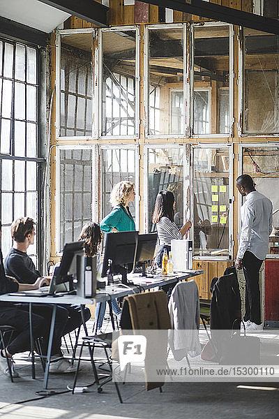 Team junger Computerprogrammierer diskutiert neue Geschäftsstrategien am kreativen Arbeitsplatz