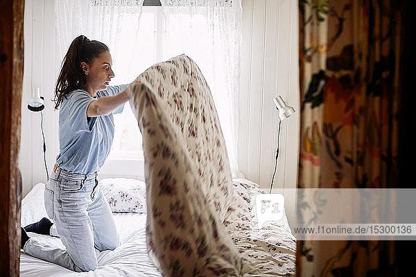 Seitenansicht einer jungen Frau  die ihre Decke zusammenlegt  während sie auf dem Bett kniend gegen ein Fenster in einem Ferienhaus kniet