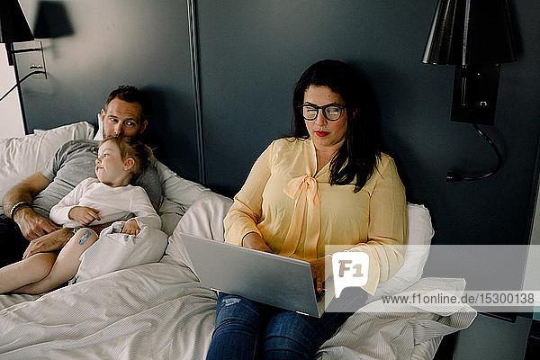 Hochwinkelansicht einer Frau am Laptop  während sie neben Mann und Tochter am Bett sitzt