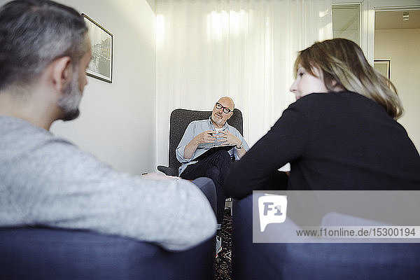 Männlicher Therapeut erklärt dem Paar während der Therapiesitzung im Gemeindezentrum
