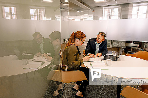 Älterer Manager erklärt Geschäftsmöglichkeiten für weibliche Kollegin im Sitzungssaal Älterer Manager erklärt Geschäftsmöglichkeiten für weibliche Kollegin im Sitzungssaal
