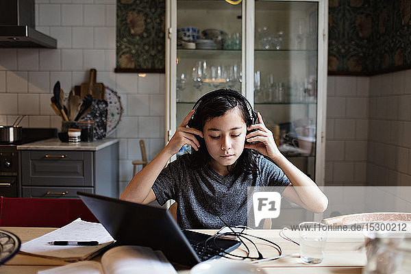 Boy using headphones while doing homework at home