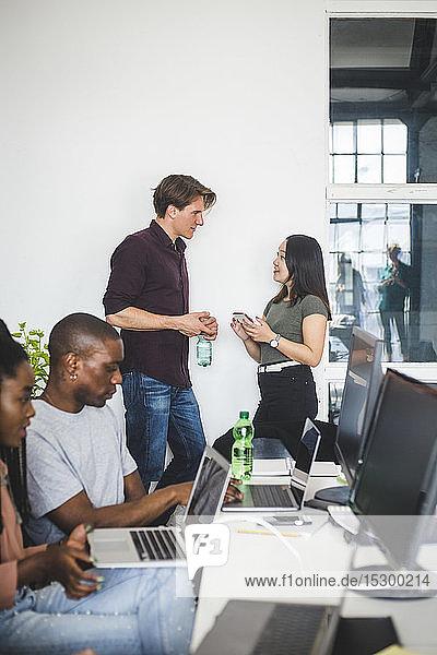 Kollegen reden an der Wand  während Computerprogrammierer im Büro programmieren
