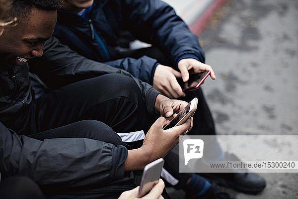 Social-Media-süchtige männliche Freunde sitzen im Winter in der Stadt auf der Straße Social-Media-süchtige männliche Freunde sitzen im Winter in der Stadt auf der Straße