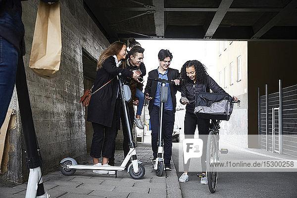 Glückliche männliche und weibliche Teenager-Freunde mit elektrischen Rollern schauen auf das Handy unter der Brücke Glückliche männliche und weibliche Teenager-Freunde mit elektrischen Rollern schauen auf das Handy unter der Brücke