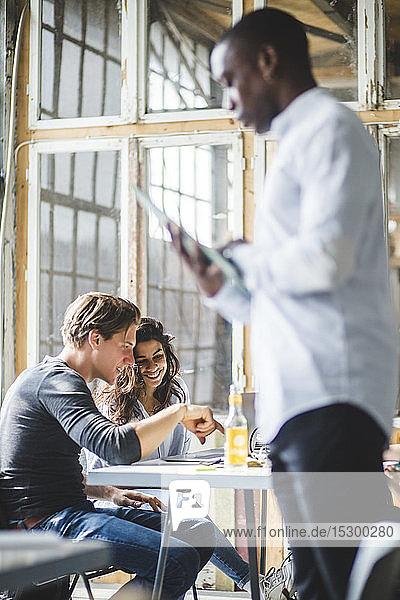 Lächelnde Computerprogrammierer mit Laptop  während ein Geschäftsmann im kreativen Büro im Vordergrund steht